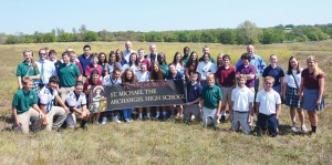 Freshmen from St. Mary's and Archbishop O'Hara high schools help announce the name of the new diocesan high school to be built in Lee's Summit, St. Michael the Archangel. With the students on a field that may one day be a football, baseball or soccer field are (L-R) John O'Connor, principal of St. Mary's and O'Hara high schools, Steve Hilliard, diocesan director of Stewardship and Development, Bishop Robert W. Finn and Dr. Dan Peters, Superintendent of Schools.  (Joe Cory/Key photo)