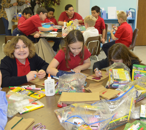 Christ the King fifth grader Elizabeth Buck and schoolmates decorate lunch bags as Valentines for the homebound on Jan. 28. (Marty Denzer/Key photo)