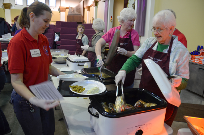 Bev Paquette juggles two plates as Ann Yoakum serves huge baked potatoes during the St. Margaret of Scotland Parish Lenten fish fry Feb. 15. (Kevin Kelly/Key photos)