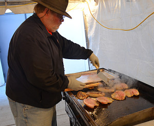 Jim Nessellrode cooks tilapia fillets on a propane-fired grill inside a tent that serves as the kitchen for St. Margaret of Scotland Parish.