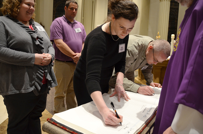 Brook Goldsmith and Brad Kavanaugh sign the Book of Elect as Erin Lear and Kevin Snyder wait during the Rite of Election and Call to Continuing Conversion Feb. 16 at the Cathedral of the Immaculate Conception. The four catechumens will be baptized, be confirmed and receive Holy Eucharist at the Easter Vigil March 30 at St. Therese Parish in Parkville. (Kevin Kelly/Key photo)