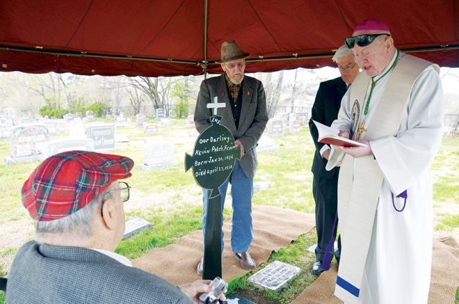 Michael Frain, left, Jack Frain and Catholic Cemetries Director Joe Harris listen as Bishop Emeritus Raymond J. Boland prays at the graveside of infant Kevin Frain, brother to Michael and Jack, who died in 1936. Harris and Cemetery Board member Dave Kopek, who also attended the April 26 service, led the effort to restore the monument that the Frain's father, Joseph, welded by hand the night before Kevin's funeral. (Kevin Kelly/Key photo)