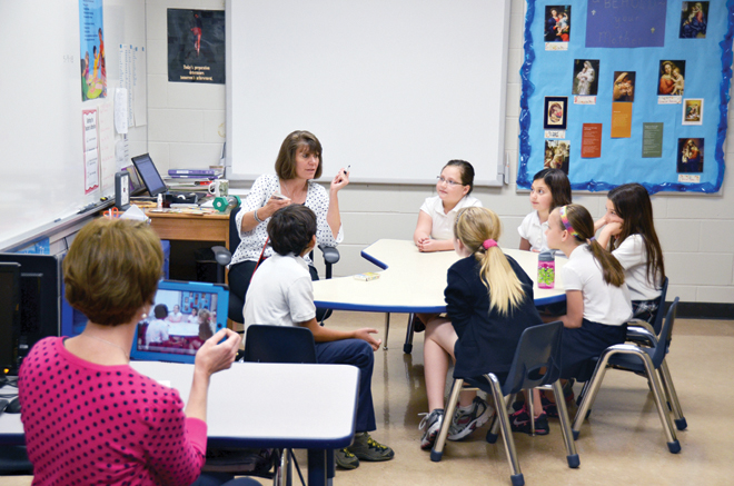 "Bridget Wood records student interaction during a game called ""Blurt!"" in DeDe Stodden's resource classroom at St. Therese School. Children who work with Stodden come in for ""just a little extra help"" or more severe learning disabilities. (Marty Denzer/Key photo)"