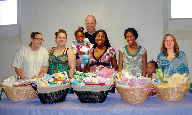 Father Matthew Bartulica and moms-to-be from The Women's Clinic in Independence at a baby shower May 19, hosted by St. Cyril's Altar Society and the Sugar Creek parish. (Photo courtesy The Women's Clinic)