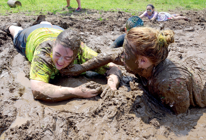 Kennedy Sartwell, of Sacred Heart Parish in Warrensburg, rubs some mud on Camp Savio staffer Jenna Prather as campers and staffers got down and muddy — and had the time of their lives — at the new diocesan summer camp for Catholic middle schoolers. (Kevin Kelly/Key photo)