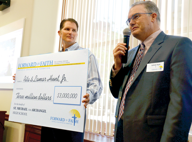 "Future Kansas City Royals Hall of Famer Mike Sweeney accepts a ""check"" from Kansas City Chiefs owner Lamar Hunt Jr, at the downtown Catholic Center June 13. The check symbolized the $3 million gift that Rita and Lamar Hunt Jr. have pledged to the Forward in Faith campaign for Catholic education and formation throughout the Diocese of Kansas City-St. Joseph. (Kevin Kelly/Key photo)"