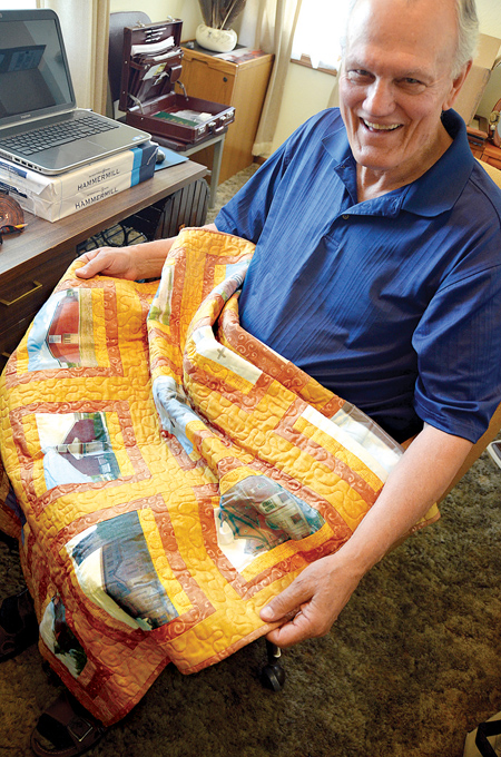 Father Ken Criqui shows off the quilt that the women of St. Mary Parish in Carrollton made for him, with pictures of every parish he has served over his 50-year career. (Kevin Kelly/Key photo)