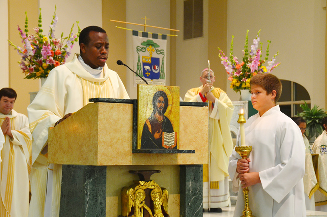 Deacon Leonard Gicheru proclaims the Gospel during the Mass at the Co-Cathedral of St. Joseph July 28 to celebrate the Year of Faith. Deacon Gicheru will be ordained next year to the diocesan priesthood. (Kevin Kelly/Key photo)