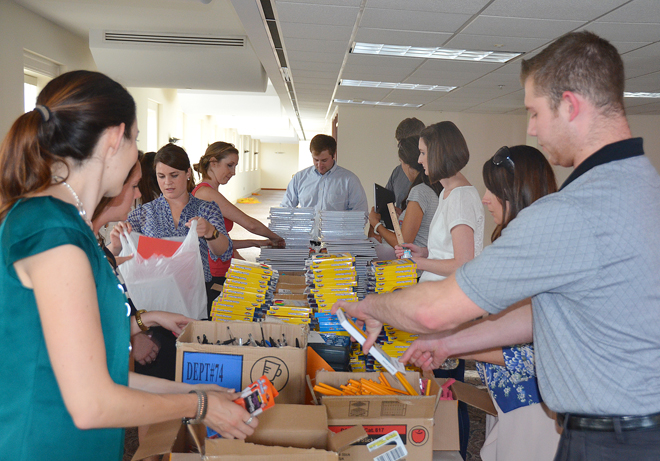 Catholic Charities' Junior Board volunteers stuff bags with school supplies for kids at Holy Cross and St. Anthony parishes and Morning Glory Cafe, Aug. 6. (Marty Denzer/Key photo)