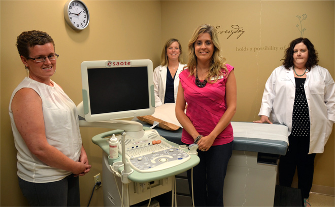 The entire staff of the Parkville Women's Clinic — Angela Clark, Lisa Murphy, Sonya Rice and Amanda Senter — show an examination room where women in crisis pregnancies can see their babies, in utero, on an ultrasound screen. (Kevin Kelly/Key photo)