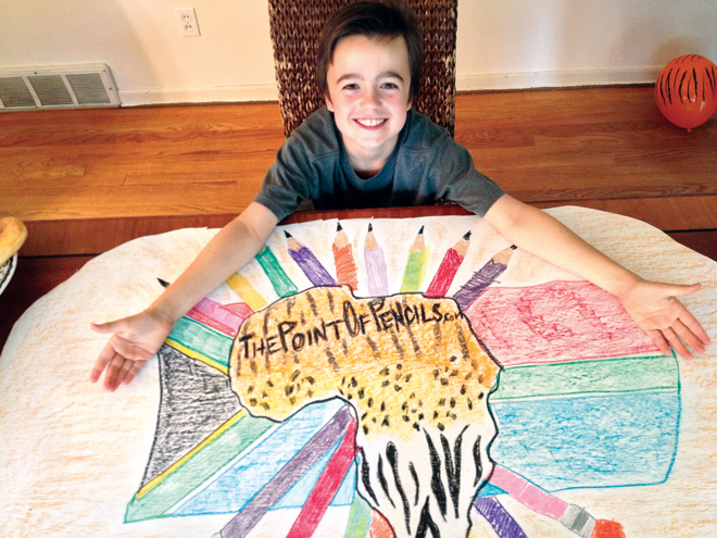 Charley McGlinn shows the poster he designed and his little sister Molly colored as part of his project to collect pencils for school children in Zambia. (Photo courtesy of Michael McGlinn)