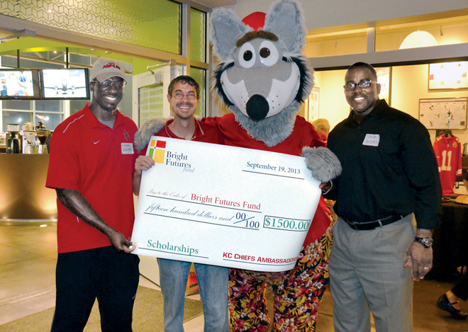 KC Wolf, flanked by former Kansas City Chiefs players, now Chief's Ambassadors, Danan Hughes and Shawn Barber, and Joe Schramp, principal of Our Lady of Guadalupe School, pose with a check payable to the Bright Futures Fund from the Chiefs Ambassadors. The check was presented to Schramp during the 3rd annual Chiefs Watch Party, Sept. 19 at the Roasterie's Bean Hangar (Marty Denzer/Key photo)