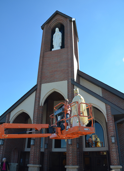 Bishop Robert W. Finn descends in a hydraulic lift that raised him 50 feet to bless the statue of Mary, Queen of the Holy Rosary, in the steeple of Holy Rosary Parish in Clinton. Bishop Finn blessed the statue following the Sept. 29 Mass celebrating the year of Faith for the southern region of the diocese. (Kevin Kelly/Key photo)