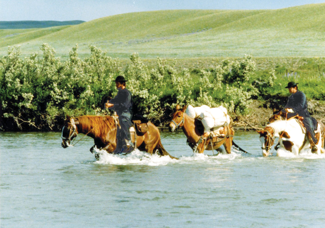 This reenactment photo makes it easy to imagine the travels and travails of the early 19th century Jesuit missionaries in Western Missouri. Jesuit Fathers Luke Larson and Pat Conroy urge their horses across a stream. (Photo: Brad Reynolds, S.J.)