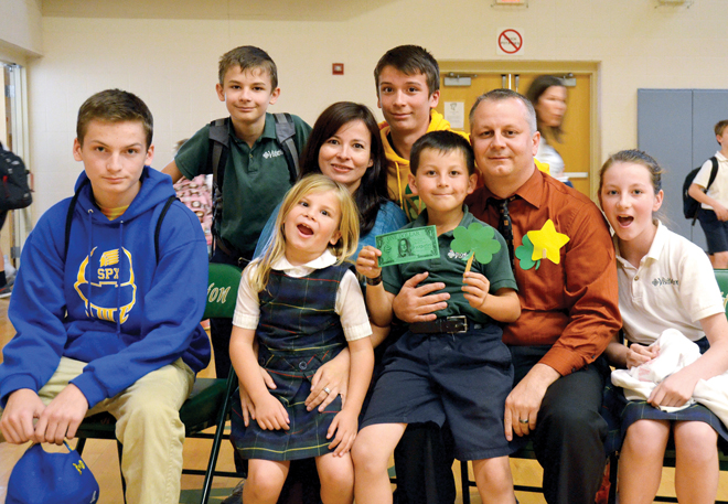 Dr. Vince Cascone, principal of Visitation School, with his wife, Mariza, and children at a surprise assembly at the school Oct. 16 to celebrate his being named a 2013 Distinguished Principal by the National Association of Elementary School Principals. (Marty Denzer/Key photo)