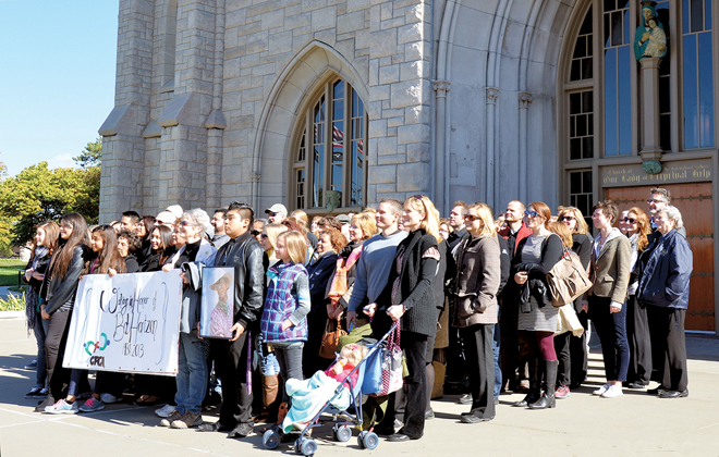 Christian Foundation for Children and Aging staff members stand in front of Our Lady of Perpetual Help (Redemptorist) Church,after walking 2.5 miles from their offices honoring CFCA founder Bob Hentzen, to attend a Memorial Mass for him Oct. 24.  (Marty Denzer/Key photo)