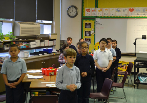 Holy Cross second graders solemnly stand for morning prayer followed by the Pledge of Allegiance. Student readers led the prayers and the Pledge over the intercom so that scenes like this were repeated in each classroom. (Marty Denzer/Key photo)