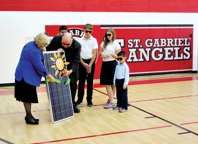 Father Joe Sharbel, pastor of St. Gabriel Archangel Parish, cuts the ribbon on a solar panel, watched by school principal Judy Marsh and students Xavier Rodriguez, Maxwell Ferrara, Rene McCullough and Brenden Cirlincuina.  (Photo courtesy St. Gabriel School)