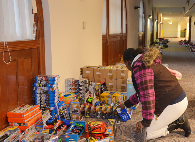 A mom looks over toys for a young boy on opening night of the Toy Shoppe.  Children's clothes, hats and scarves are stacked in the hallway behind her. (Marty Denzer/Key photo)