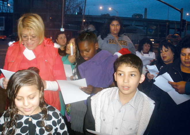 Students, teachers and parents of Our Lady of Guadalupe School gather to sing a verse of the Posadas song at restaurants on Southwest Blvd., Dec. 19. Las Posadas is a traditional celebration recalling the difficulties Mary and Joseph had finding lodging in Bethlehem, and so found shelter in a stable. There, Jesus was born. (Marty Denzer/Key photo)