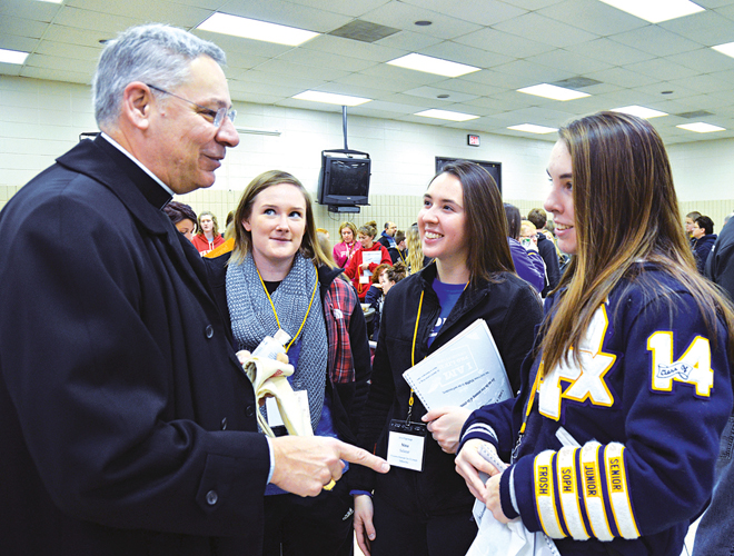 Bishop Robert W. Finn speaks with St. Pius X High School seniors Emma Haas, Nina Salazar and Olivia Jackson Jan. 20 before he offered his prayers and blessings to the 200 people who boarded four buses for the annual March for Life in Washington, D.C. (Kevin Kelly/Key photo)