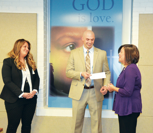 Jackie Loya-Torres of the Women's Foundation of Greater Kansas City, presents a check for $25,000 to Jarrod Sanderson, Catholic Charities Director of Family Supportive Services Jan. 14 while Nicole McCrory, Services of Pregnant Women, looks on. The funds will be used for the Women's Economic Empowerment Program, including class materials, employment assistance and things like child care, bus passes or wardrobe assistance to help women find a job.  (Marty Denzer/Key photo)