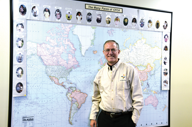 Scott Wasserman, who took the reins of Unbound, formerly Christian Foundation for Children and Aging, just a few weeks ago, stands in front of a map showing the many developing countries around the world. Living in those countries are the more than 300,000 children, elderly and families supported by sponsors through the organization. Photos of some of the sponsored frame the map. (Marty Denzer/Key photo)