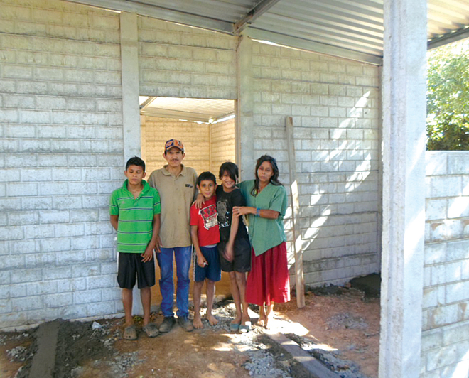 Irma and some of her children stand in front of their new home in the impoverished village of Chiltiupan, El Salvador. The home was the gift of priests of the Diocese of Kansas City-St. Joseph and the Archdiocese of Kansas City in Kansas in recognition of the love shown to them by Bob Miller, who died four years ago, and his family who continue their tradition of service to the poor. (Photo courtesy of Sean Miller)