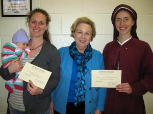Dr. Judith Wylie is flanked by Louise Landry with baby Ruby and Sister in Jesus the Lord Faustina Marie Goedkin as they show off their Montessori Teacher Training certificates. The Jan. 4 celebration honored them and wished Sister Faustina Marie 'Bon Voyage.' She was to take her skills to Vladivostok, Russia, to work with orphans. (Photo courtesy of Dr. Judith Wylie)