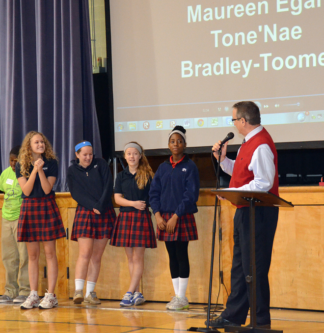 Superintendent Dr. Dan Peters offers a congratulatory word to the winning team of (from left) Zoe Butler, Maureen Egan, Anna Campbell and Tone'nae Bradley-Toomer at a pep rally for Brain Sports on Dec. 19. (Joe Cory/Key photo)