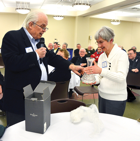 John Massman presents Katy Crabtree with a Waterford crystal vase in recognition of her years of service as wellness coordinator for priests, and especially her service to the diocese's retired priests. The surprise presentation was made at a gathering of retired priests Feb. 27 at Visitation Parish in Kansas City. (Kevin Kelly/Key photo)