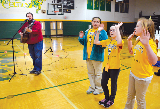 From left, Ashlyn Alexander, Kaitlyn Vaught and Tori Allen of St. Gregory Barbarigo School in Maryville help singer-guitarist Joe Peterson lead hundreds of Catholic fifth graders through songs at the annual Vocations Days Feb. 27. (Kevin Kelly/Key photo)