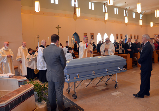 Bishop Robert W. Finn blesses the casket of Father Donald Cleary with holy water before the retired priest's funeral Mass March 4 at Our Lady of Lourdes Parish in Harrisonville. Father Cleary was pastor of the parish for nine years from 1983 to 1992. (Kevin Kelly/Key photo)
