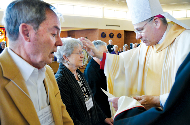 Vince Thomey and Phil Patton sign the Book of the Elect at the March 8 Rite of Election and Call to Continuing Conversion at the Cathedral of the Immaculate Conception in Kansas City. They will be entering the church at Easter Vigil at St. Joseph the Worker Parish in Independence. (Kevin Kelly/Key photo)