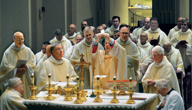 Bishop Robert W. Finn consecrates the Eucharist at the Memorial Mass for Bishop Raymond J. Boland at the Cathedral of the Immaculate Conception. Among the bishops concelebrating  was Bishop Emeritus Kevin Boland of Savannah, Ga., right, brother of Bishop Raymond. (Joe Cory/Key photo)