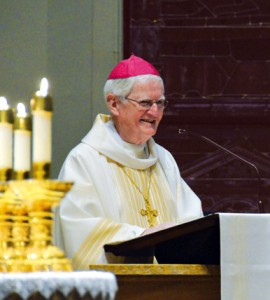 Bishop Emeritus Kevin Boland laughes while describing his brother during the homily. (Joe Cory/Key photo)