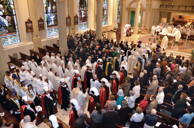 A long line of bishops process through an honor guard of Knights of Columbus and Knights of Peter Claver at the opening of the Memorial Mass for Bishop Raymond J. Boland. (Joe Cory/Key photo)