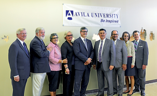 President Ron Slepitza (center), Avila trustees and  officers stand in front of the wall in Bundschu Library that they just knocked holes in to symbolize a breakthrough in learning on March 31. The library will be renovated, digitized and will offer state of the art technology, class and group study rooms and areas for quiet study. It will be finished this coming August. (Marty Denzer/Key photo)