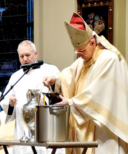 Bishop Finn pours balsam into the Oil of Chrism. (Kevin Kelly/Key photo)