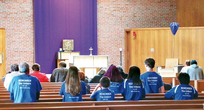 Members of the LIFE Runners and supporters take time from their 'Run A-Cross America' to pray the Rosary at St. Charles Borromeo church in Kansas City. (Photo courtesy of John Heuertz)