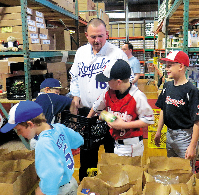 Kansas City Royals designated hitter Billy Butler spent his day off April 28 sacking groceries for the poor at Bishop Sullivan Center's midtown St. James Place with special help from area little leaguers. (Kevin Kelly/Key photo)