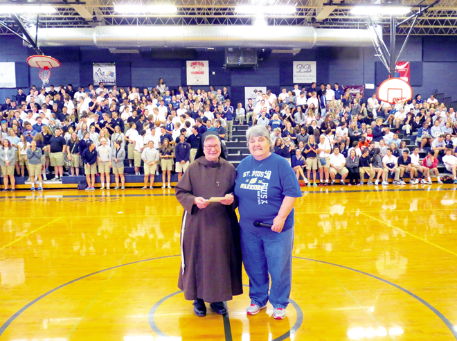 Barbara Witherow, cafeteria director of St. Pius X High School, presents checks totaling $8,500 April 28 to Franciscan Sister Andrea Kantner to help the order ship medical equipment and other supplies to the poor throughout the world. (Kevin Kelly/Key photo)