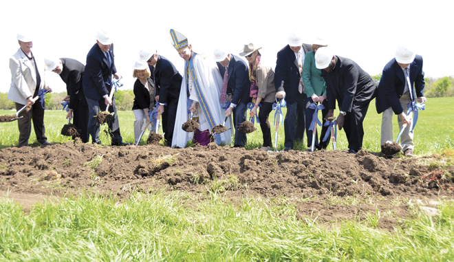 Bishop Robert W. Finn, flanked by supporters of St. Michael the Archangel High School, ceremonially break ground at the 80 acre site for the new school in Lee's Summit, May 3. (Joe Cory/Key photo)