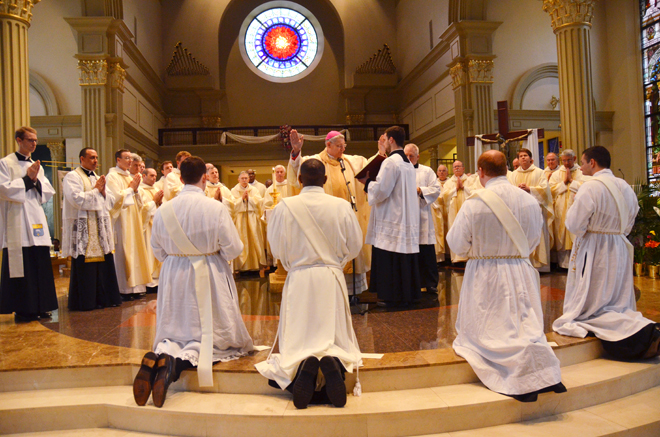 The diocese's four newest priests kneel before Bishop Robert W. Finn and the priests of the diocese at their May 24 ordination. They are from left, Fathers John Fitzpatrick, Leonard Gicheru, Daniel Gill and Eric Schneider. (Kevin Kelly/Key photo)