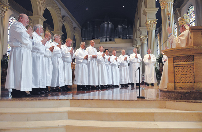 Thirteen candidates about to be ordained receive their final questions from Bishop Robert W. Finn before their ordination as permanent deacons June 7 at the Cathedral of the Immaculate Conception. From left, they are Richard Boyle, Daniel Brink, Marcelino Canchola, James Dougherty, Richard Gross, Tyrone Gutierrez, Keith Hoffman, John Nash, Dien Nguyen, James Olshefski, John Purk, Douglas Warrens and John Wichmann. (Kevin Kelly/Key photo)