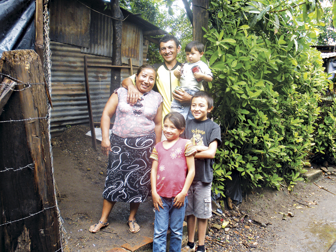 Faustina and Carlos Menjivar stand outside their home in Community Manuel II, an urban-rural area near Santa Ana, with their children, Omar (11) sponsored through Unbound (formerly C.F.C.A.), Karla (8) and baby Gabriel (2). The community is on an abandoned rail yard, and the tracks run along the dirt road. (Marty Denzer/Key photo)