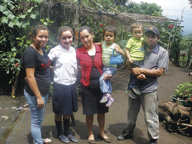 Marlena (holding a neighbor's child) with daughters Elvira and Wendy, husband Julio and son Julio Cesar, stands near a garden planted near their front door. (Marty Denzer/Key photo)