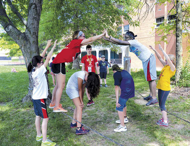 In a Camp Savio exercise that emphasizes teamwork and trust, Brianna Munsterman of Sacred Heart Parish in Warrensburg and Margaret Banlon of St. John Francis Regis Parish in Kansas City walk across a double tightrope. (Kevin Kelly/Key photo)