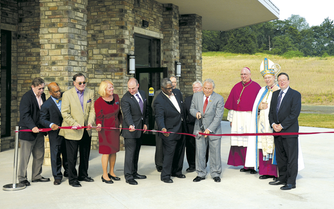 Kansas City–St. Joseph diocesan Bishop Robert W. Finn and Archbishop Joseph F. Naumann of the Archdiocese of Kansas City in Kansas join city and business dignitaries at the ribbon cutting and grand opening ceremonies for Phase I of St. Michael's Veterans Center June 30. The Center, which will provide permanent housing and a full spectrum of services to homeless and at-risk veterans from all branches of the military, was officially opened by the ribbon cutting ceremony. Kansas City Mayor Sly James, Jackson County Executive Mike Sanders, Housing Authority Board Chair Donovan Mouton, former Catholic Charities CEO Mike Halterman and other guests helped St. Michael's Veterans Center Board Member Art Fillmore cut the ribbon.  (Marty Denzer/Key photo)