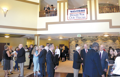 Veterans and families, city officials and other guests attending the grand opening of St. Michael's Veterans Center chat in the Grand Lobby under the sign 'Welcome, Homes for Our Heroes.' (Marty Denzer/Key photo)